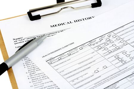 questionnaire: Two insurance forms on a clipboard with a pen.