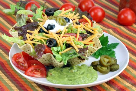 Taco salad in a corn taco bowl surrounded with tomatoes, jalapino peppers and guacamole.