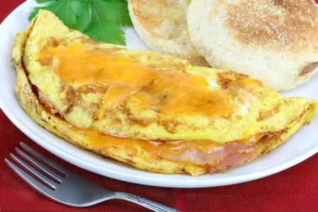 An omelet with ham and cheddar cheese on a white plate with an English muffin.