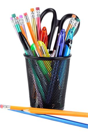 Black metal pencil cup filled with colorful pencils, pens and a pair of scissors.  On white with copy space.