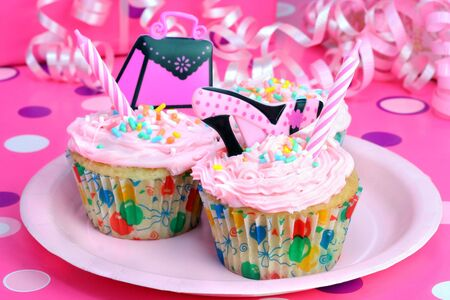 Pretty pink frosted party cupcakes with a feminine theme. photo