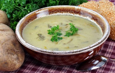 A bowl of potato leek soup, garnished with parsley, surrounded with fresh potatoes, bread and parsley.