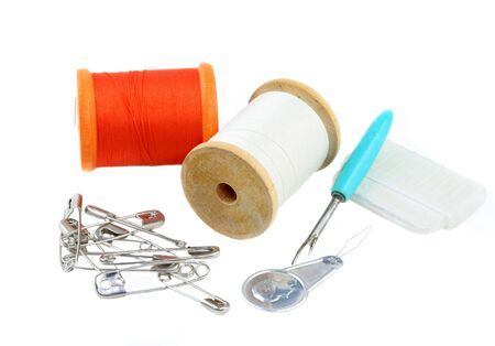 ripper: Vintage sewing supplies including wooding thread spools, safety pins, seamstress chalk, threader, and a seam ripper. On white with copy space.