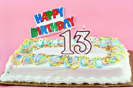 Festive birthday sheet cake with the number 13 lit candles.  Pretty pastel colors with a Happy Birthday sign in the background. 版權商用圖片
