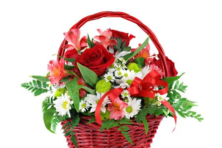 A beautiful red wicker basket filled with assorted flowers including daisies and roses.  On white with copy space.