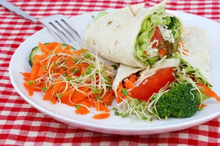 A healthy vegetable wrap with a side of shredded carrot salad. photo