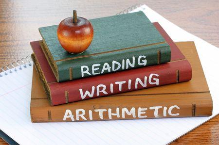 lectura y escritura: De madera con tres libros de lectura, escritura y aritm�tica pintada sobre ellos spriral sentado en un block de notas.