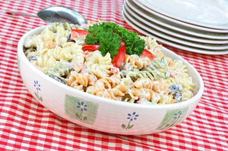 Pasta salad with twirled macaroni, tomatoes and olives.  Checked picnic tablecloth and additional serving plates. Stock Photo