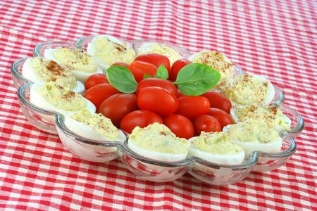 A plate of deviled eggs with grape tomatoes and fresh basil.  Plate is on a red and white checked picnic tablecloth. Stock Photo - 5228452