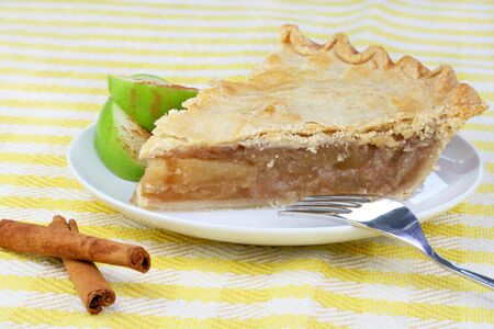 One slice of apple pie on a plate with Granny Smith apple slices. photo