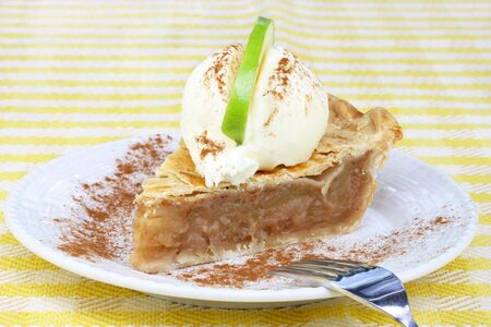 granny smith apple: One slice of apple pie with vanilla ice cream on top and a slice of a Granny Smith apple for garnish.