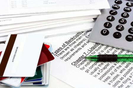 A bankruptcy document laying on a table below a calculator, bills, and a stack of credit cards.  Copy space available on top blank credit card. Stock Photo - 5292374