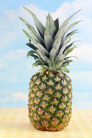 One whole golden pineapple against a cloudy sky. Reklamní fotografie