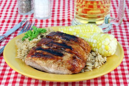 Barbecued country style spare ribs on a plate with corn and brown rice.   photo