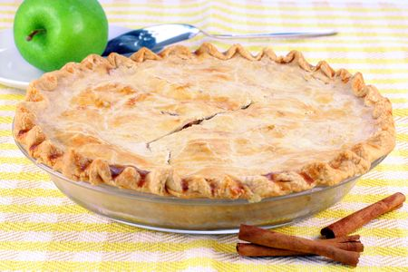 granny smith apple: One whole homemade apple pie with cinnamon sticks and a granny smith apple to the side.