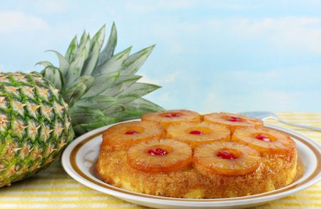 Pineapple upside down cake with a fresh whole pineapple to the side.  Blue sky background has copy space.