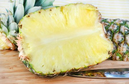 One pineapple sliced in half lengthwise with top and other section in background.  Knife with reflection under pineapple. Stock Photo - 5335614