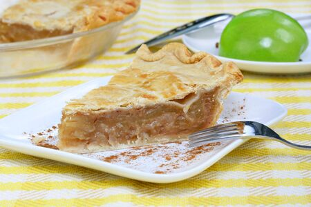 granny smith apple: One slice of fresh baked apple pie on a table with cut pie and Granny Smith apple.