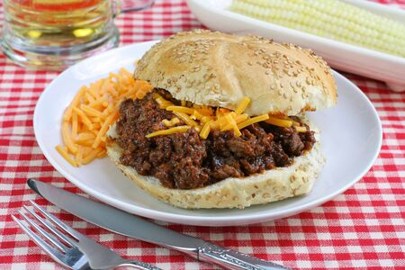 Close up view of a Sloppy Joe sandwich with cheddar garnish.  Corn and a beer in the background.