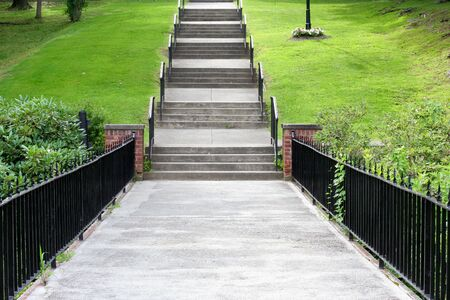 grassy knoll: A walkway leading to concrete steps up a grassy knoll.