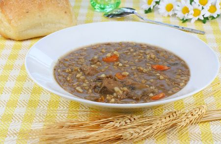 Beef barley homemade soup and fresh bread in a pretty table setting. photo