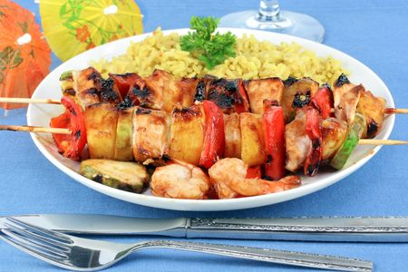Skewered shrimp, pineapple, chicken and assorted vegetables on a plate with curried rice.