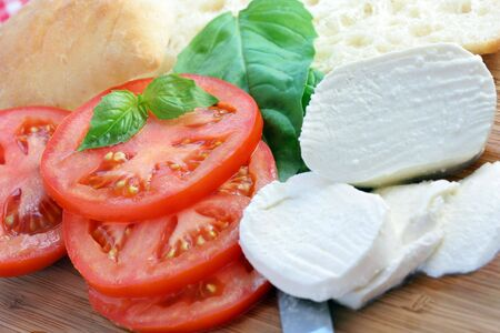 Fresh sliced tomatoes, bread, fresh mozzarella and basil-all the makings for a panini. Stock Photo - 5492878