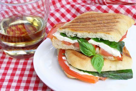 One pannini sandwich of fresh basil, tomatoes and mozzarella cheese.