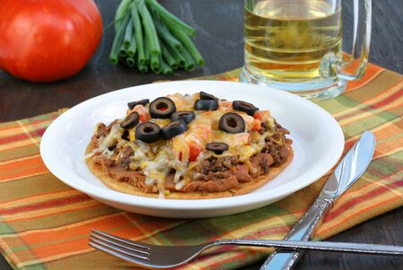 One Mexican Pizza made with a Gordito, beef, refried beans,tomatoes, olives, cheese and scallions. Stock Photo - 5576353