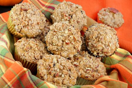 Full basked of pumpkin and pecan muffins with streusel topping.