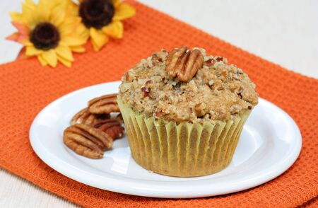One pumpkin pecan muffin with streusel topping with pecans on the side. Stok Fotoğraf