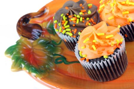 Fal frosted chocolate cupcakes on a pumpkin plate.  White background with copy space. photo