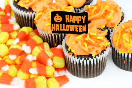 Orange iced chocolate cupcakes and candy corn with a Happy Halloween flag. photo