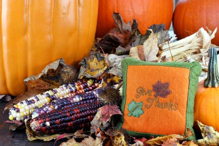 Handmade Give Thanks pillow accents assorted fall items, including Indian Corn and pumpkins. photo
