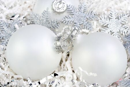 shredded paper: Three white Christmas ball ornaments nestled in white paper with silver stars. Stock Photo