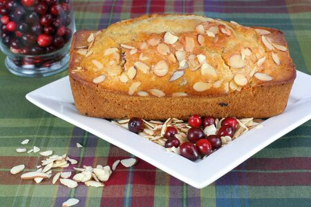 A cranberry almond loaf on a plate with fresh cranberries and sliced almonds. photo