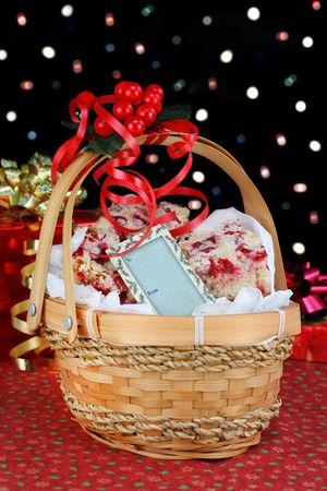 canastas con frutas: Una cesta de Navidad lleno de cookies de la barra de ar�ndano rojo y una etiqueta en blanco. En frente de las luces de bokeh de vacaciones.  Foto de archivo