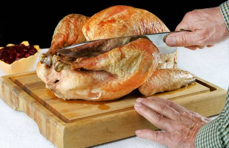 Roast turkey on a cutting board with hands and knife cutting into the leg.  Black background with copy space. Stock Photo