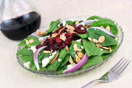 Glass plate of fresh spinach, feta cheese, vidalia onion slices, almonds and dried cranberries.  A pretty
