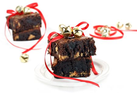 Chocolate fudge and peanut butter brownies on a white background wrapped in red ribbons and golden bells for Christmas gift giving.