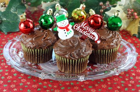 Chocolate cupcakes decorated for Christmas with a snowman, Christmas ornaments and a Merry Christmas pick.  Festive background and tablecloth. Stock Photo - 5889294