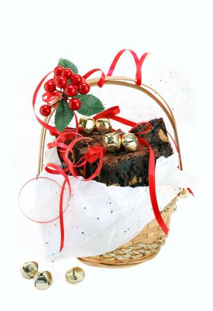 brownies: Fudge brownies with peanut butter chips fill a festive Christmas gift basket.  Red bows and golden jingle bells with sparkly tissue paper decorate the basket.