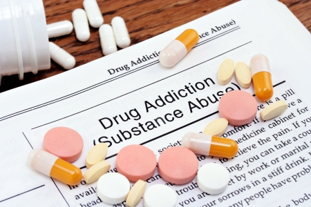 Information on drug addiction or substance abuse with varius pills scattered over the page. Close up macro shot. Banque d'images