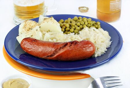 Knockwurst, peas, and sauerkraut with a beer for dinner. photo