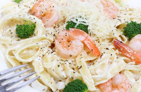 Shrimp and fettuccini alfredo with broccoli in a macro image.