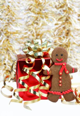 One colorful gingerbread man cookie with a red scarf standing next to a red Christmas gift. photo