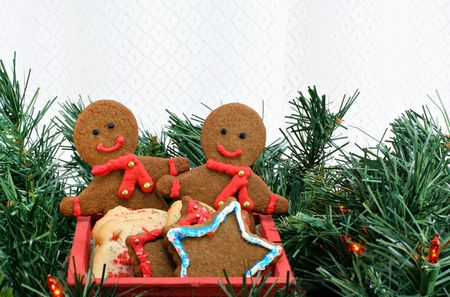 Two homemade gingerbread men in a wooden cart,  with assorted cookies, surrounded by Christmas greens and lights. Stock Photo - 5936529