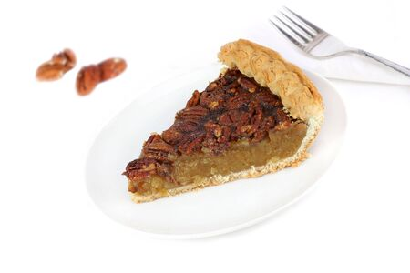 One slice of homemade pecan pie on a white tablecloth with copy space. Stock Photo