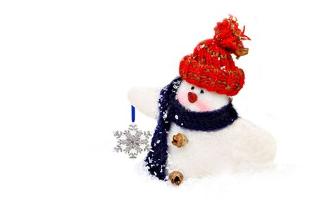 Handmade, woolen snowman with cap and scarf in the snow carrying a snowflake.  On white with copy space. photo