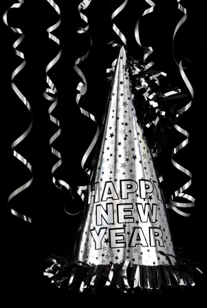 Silver Happy New Year party hat isolated on black with silver streamers.
